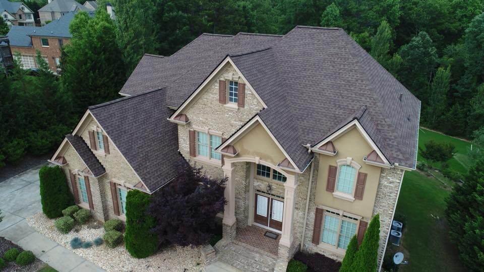 Arial photo of two story home with a third story loft area in the main section of the home. The multi level roof structure sports a series of pitch dormers inset within one another and a pyramid main roof for the central portion of the home. The house has brown asphalt tiles with a red accent color. The home facade is brown painted stucco and light stone