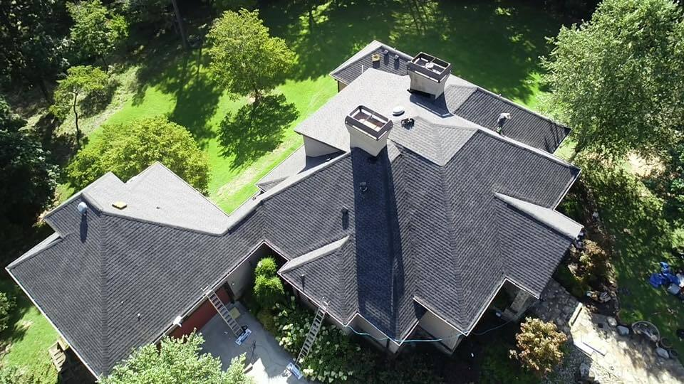 aerial photo of roof from almost dirctly above. The roofline shows a very high pitch roof with flat area at the peak. The roofline is pyramid shaped as it descends to dormers that surround the four sides of the main home. An enclosed breezeway leads to a multi-car garage that has the same pyramid roofline with a steeper pitch from the top as it does not have the flat area of the main building.
