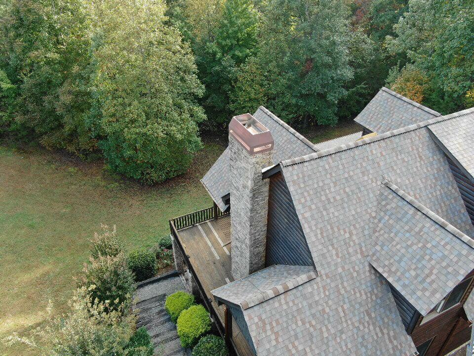 aerial photo of an expansive home with multiple pitched dormers with brown and blue tiles