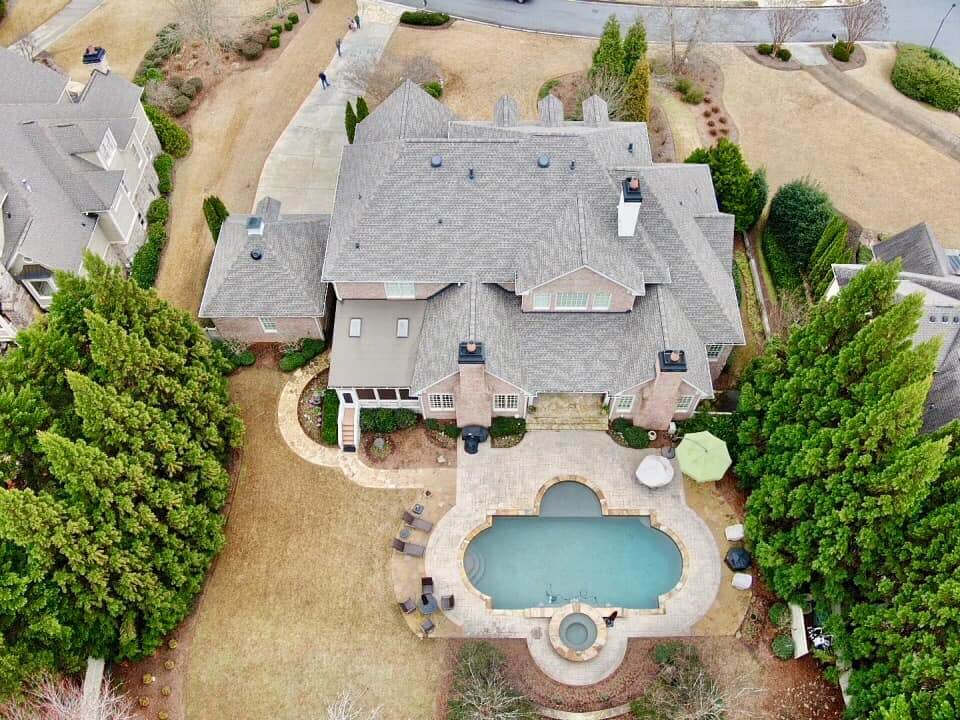 Aerial photo of estate home with large in ground swimming pool in back yard.