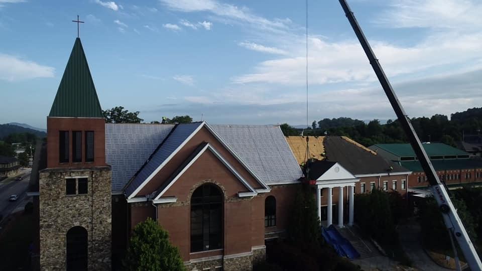 photo of crane assisting with unloading old asphalt tiles