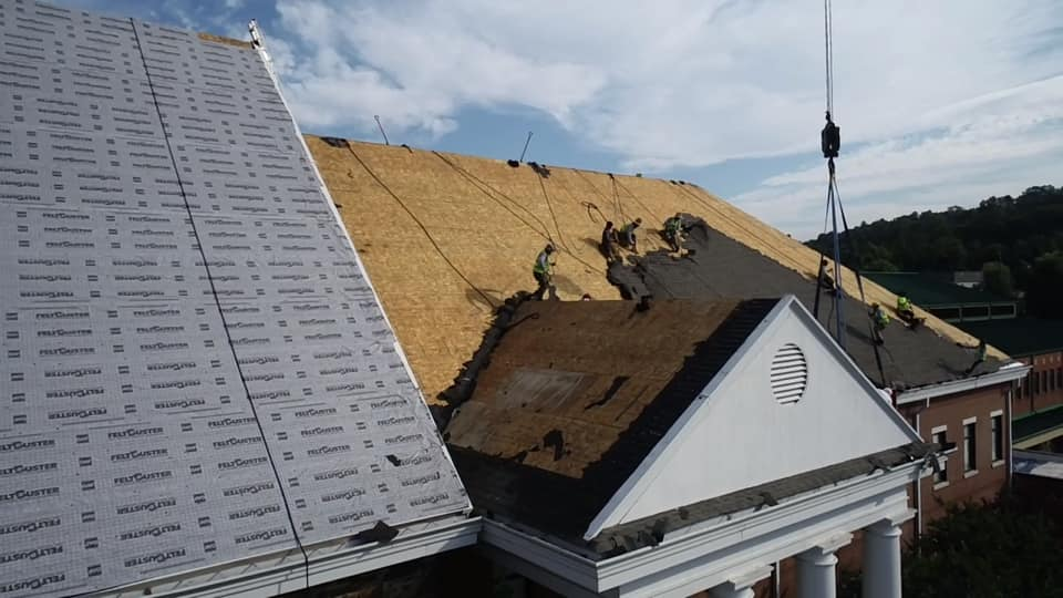 Aerial view of new roof underlay sections with one section of roof with team working to remove old roof materials
