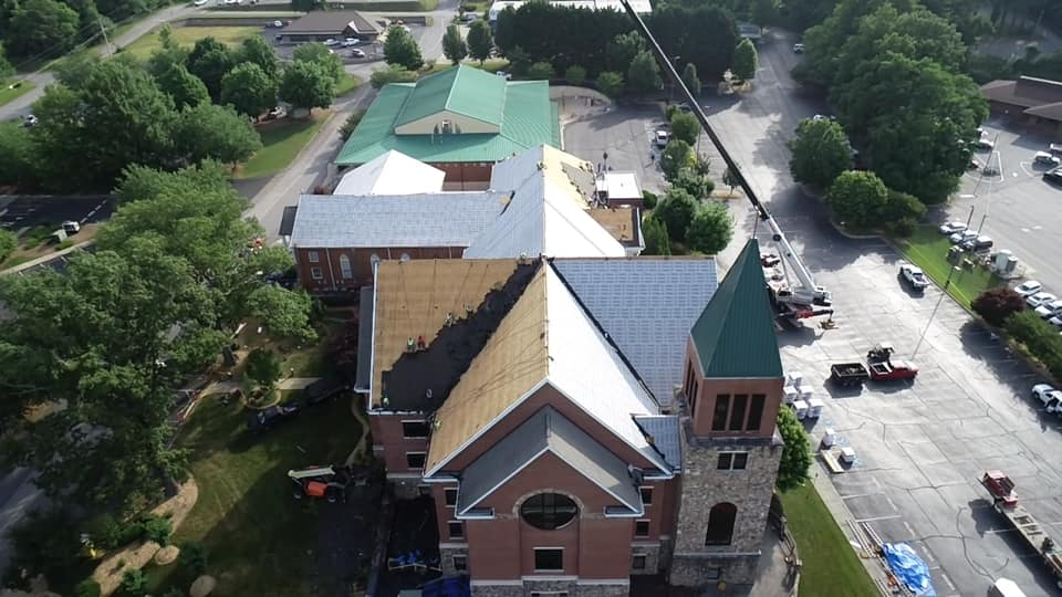 aerial photo of roof with the last of the old roof being removed and the new underlay on the majority of the roof.
