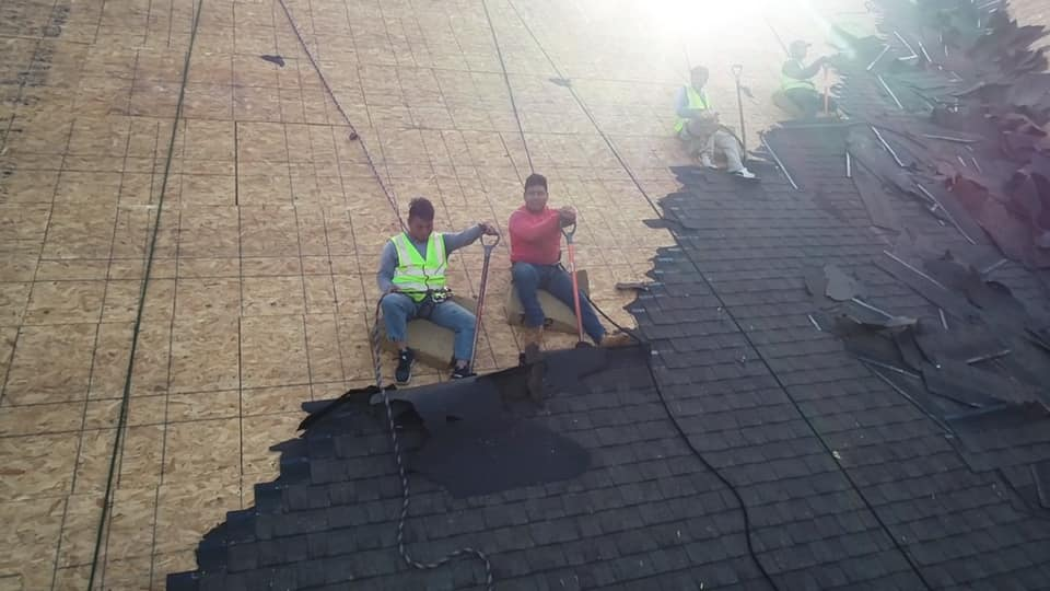 close up aerial photo of Ridgeline team on the roof at work removing the old roof