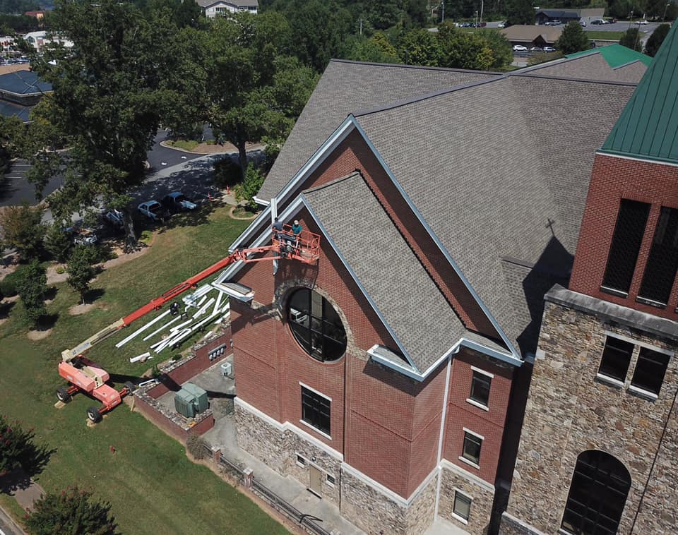 aerial photo of edging and trim work on front of church using the crane to hoist team and equipment and materials
