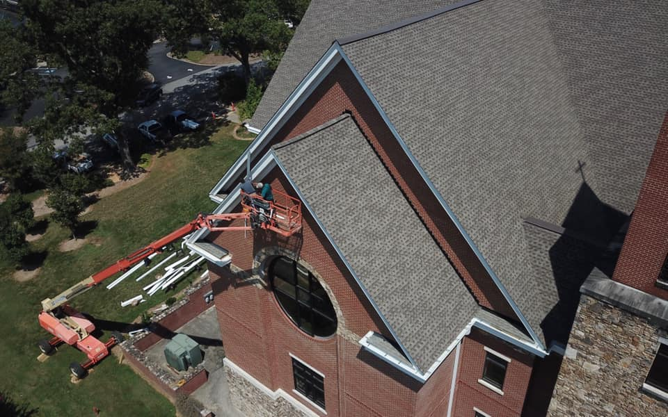 aerial photo of team on crane installing the edging and finishing sides of the new roof.