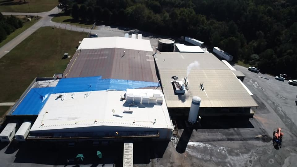 longer view of plant with large sections of blue tarps covering the damaged areas of the roof