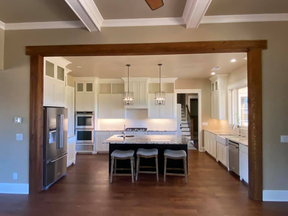 photo of chef's kitchen in the Boone House. It shows the entire wet bar kitchen Island with seating for three at the granite countertop, on the right the farm sink with large windows, the rear wall with range and ovens surrounded by floor to ceiling cabinets and on the left the french door refrigerator. Pendant lighting and wood floors.