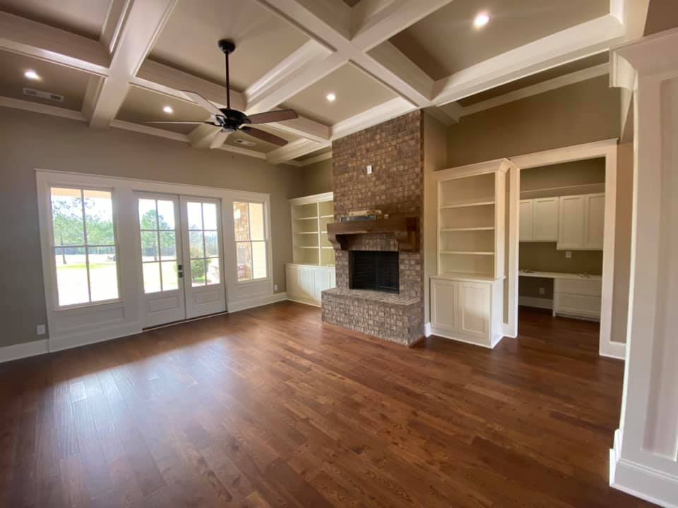 wide view photo of great room in The Boone House in Oconee, GA, with brick fireplace, channeled ceiling, hardwood floors and dual built in book cases