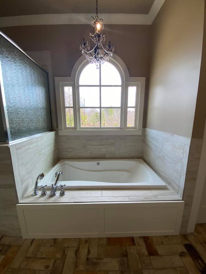 Photo of master bedroom soaker tub with chandelier and arched window
