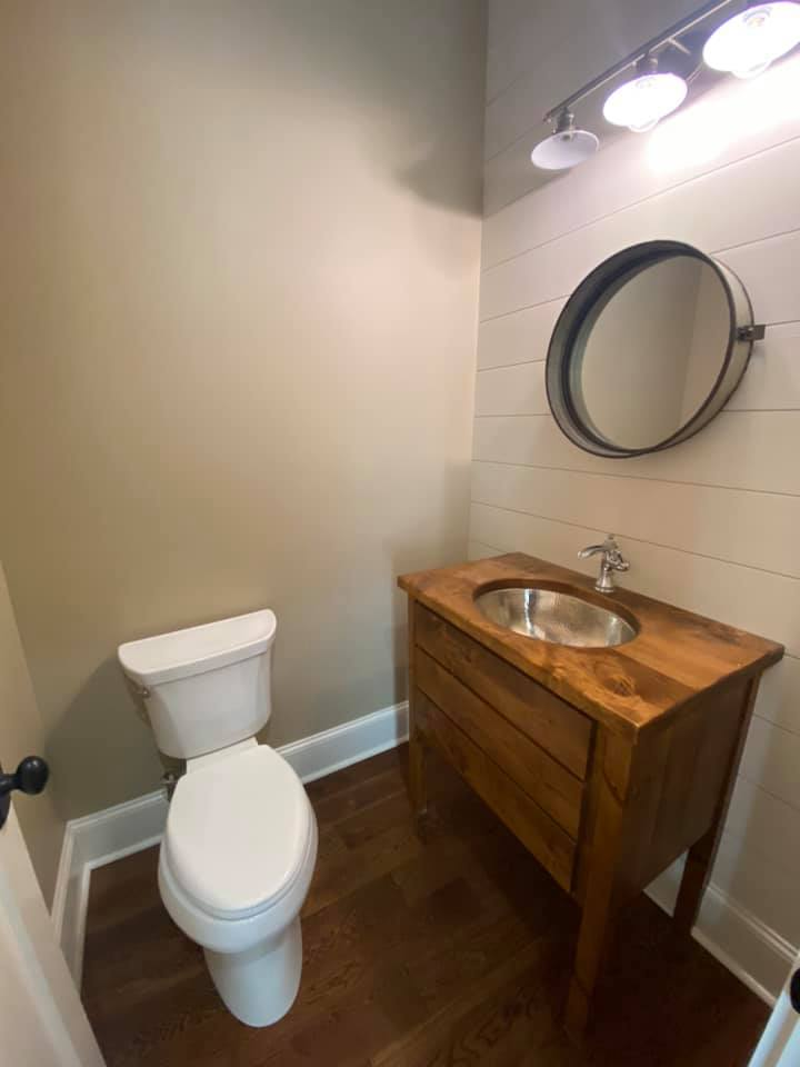 Photo of gust bath with rustic sink and mirror. large beadboard wall and rustic lighting