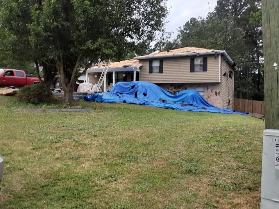 Photo of front of home undergoing roof replacement
