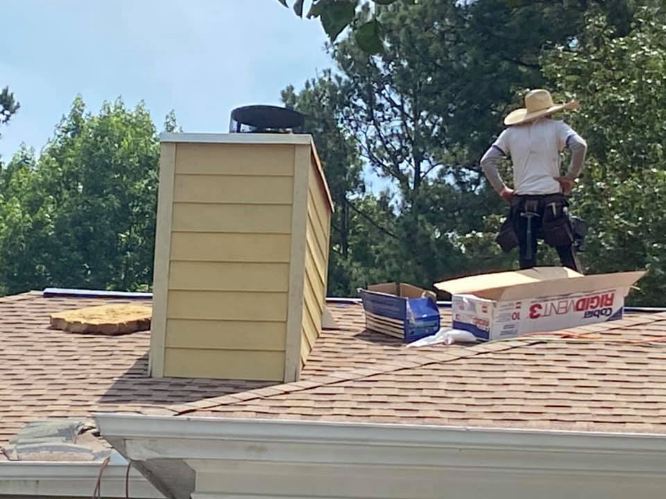 new roof materials being installed around a chimney stack