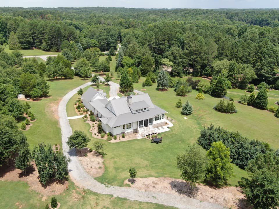aerial view of the estate property with the home in a new metal roof