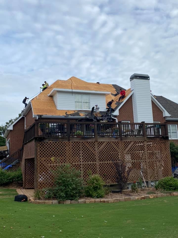 photo of rear of Watkinsville home with workers starting to install underlay system