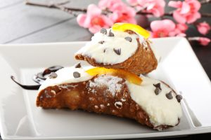 Cannoli from Sicily, with ricotta cream and crispy wafer on complex background