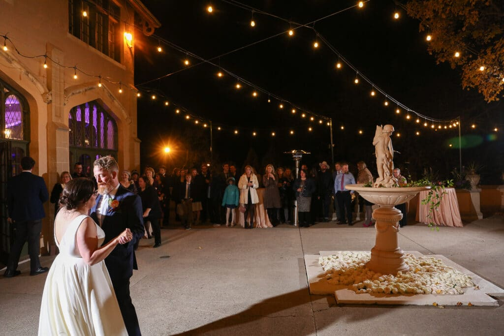 bride and groom dance on the outdoor terrace at fowler house mansion, next to rose-filled fountain