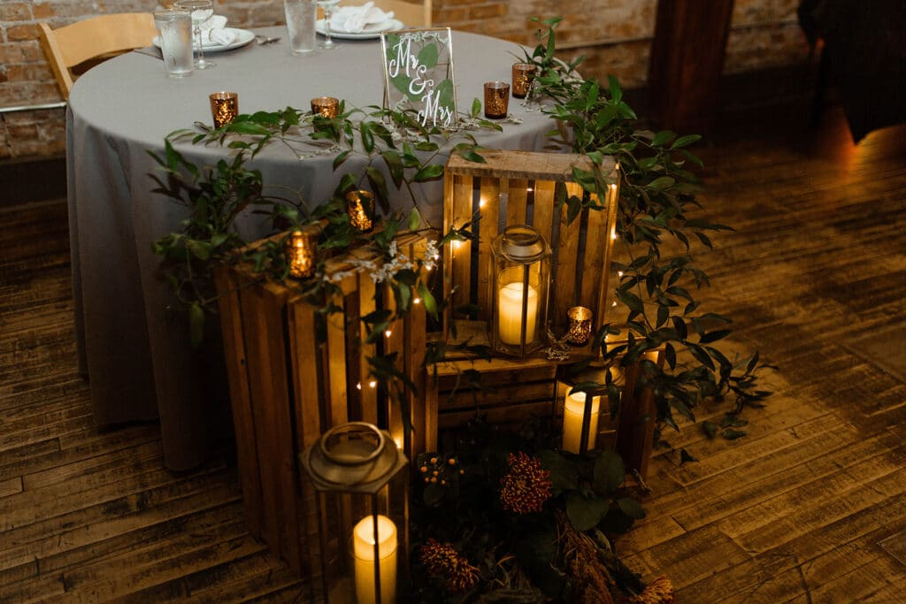 smilax greenery on sweetheart table with lanterns and rustic decor
