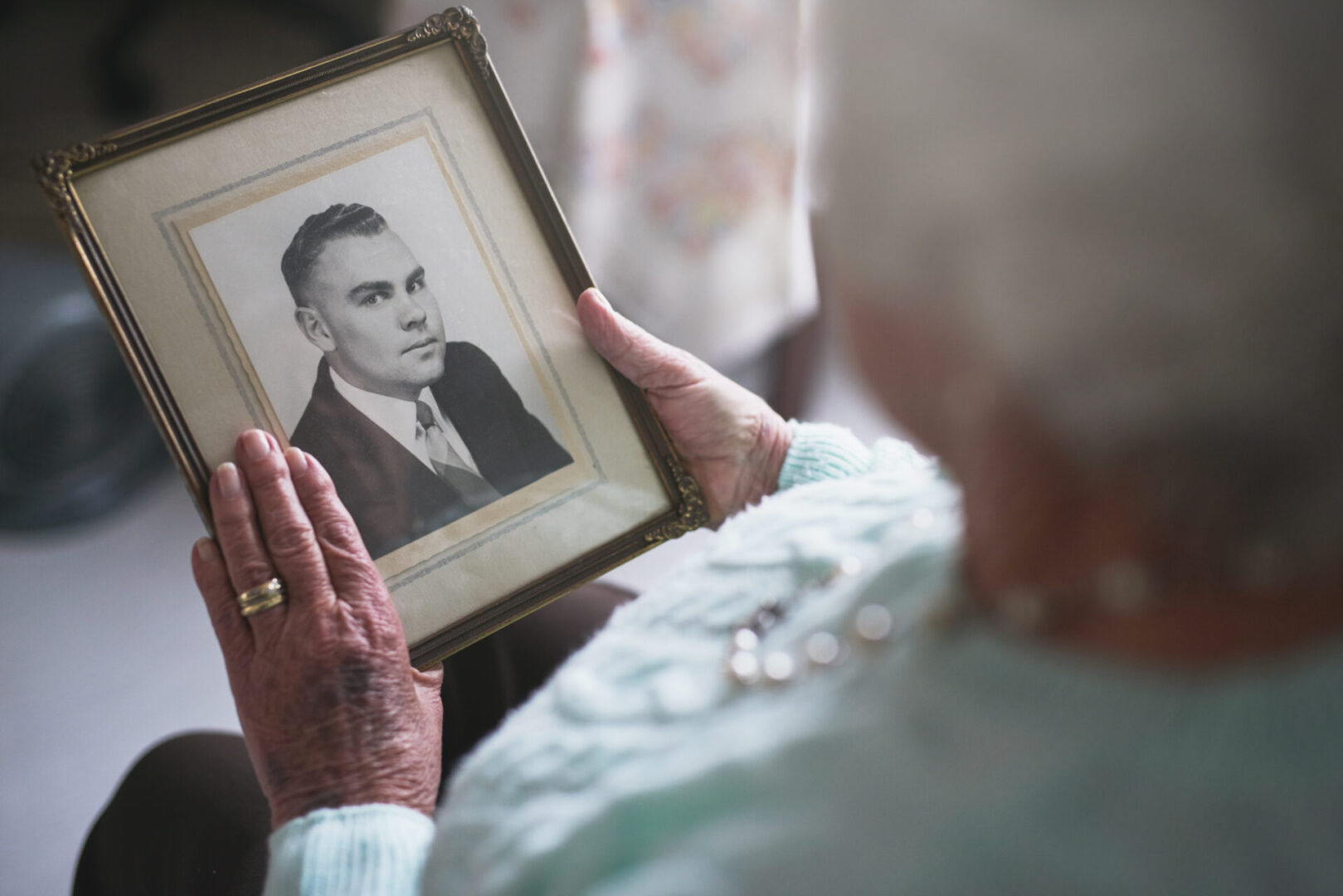 Cropped shot of a senior woman looking at an old black and white photo of a man