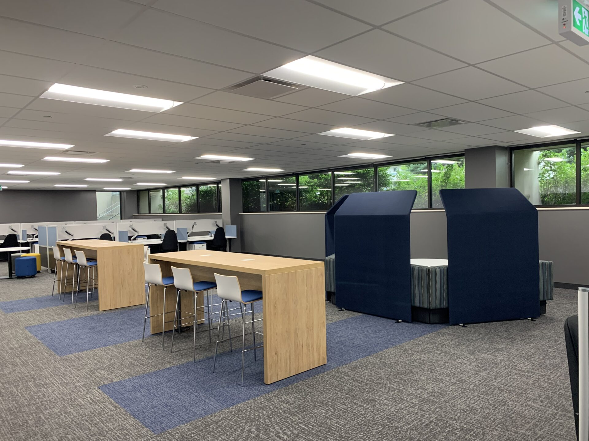 Interior office space showing bar-height collaboration spaces and individual workstations in the background