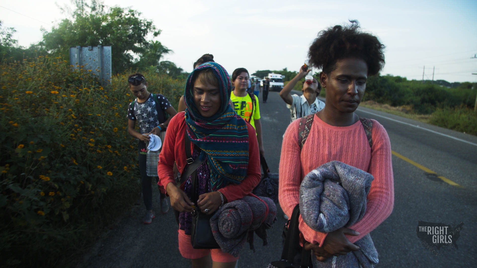 Women walking along road trying to hitch rides as they go.
