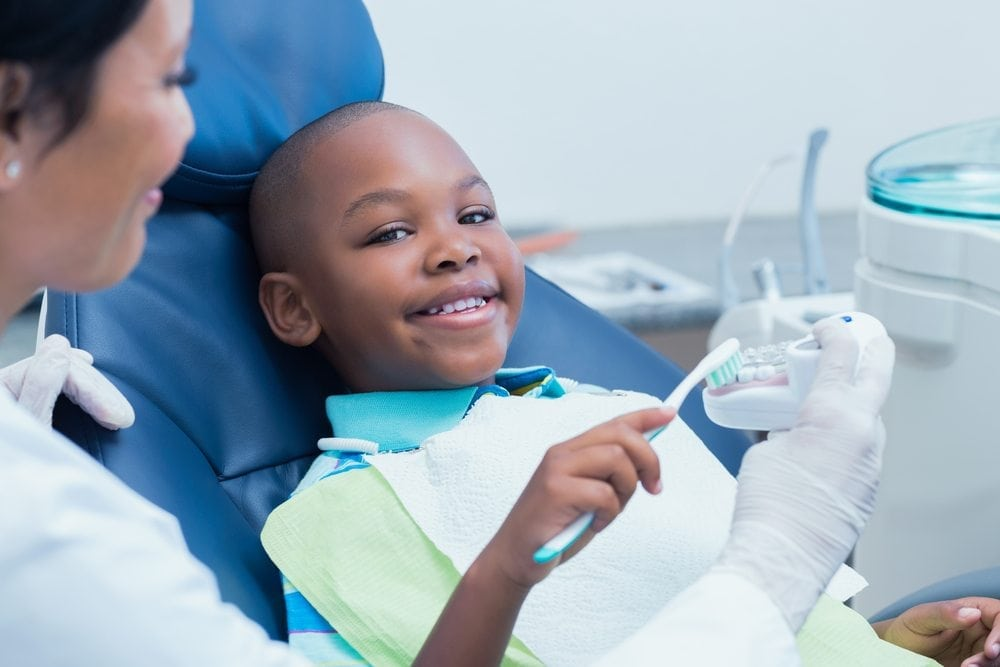 young boy smiling while brushing fake teeth at the dentist