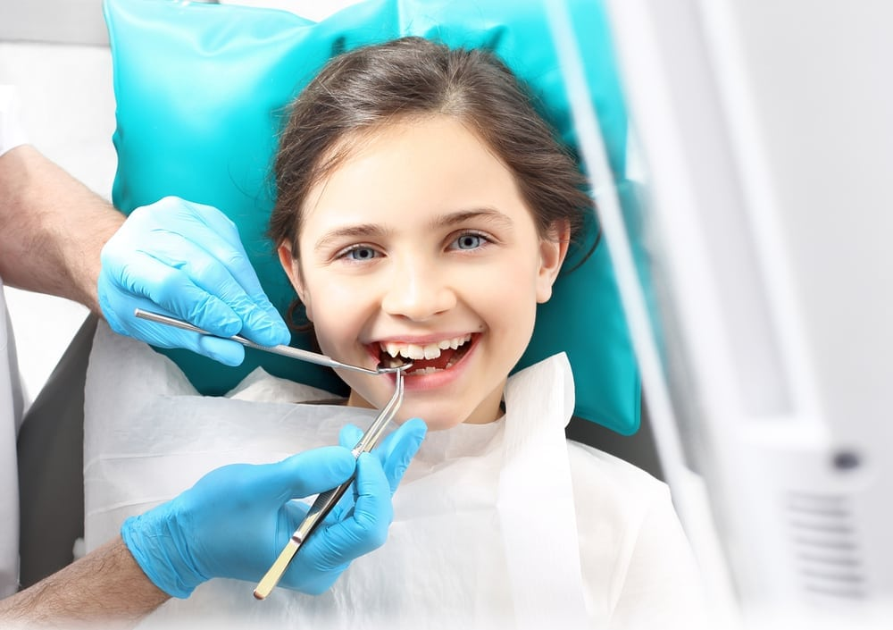 young girl on dentist chair getting her teeth cleaned
