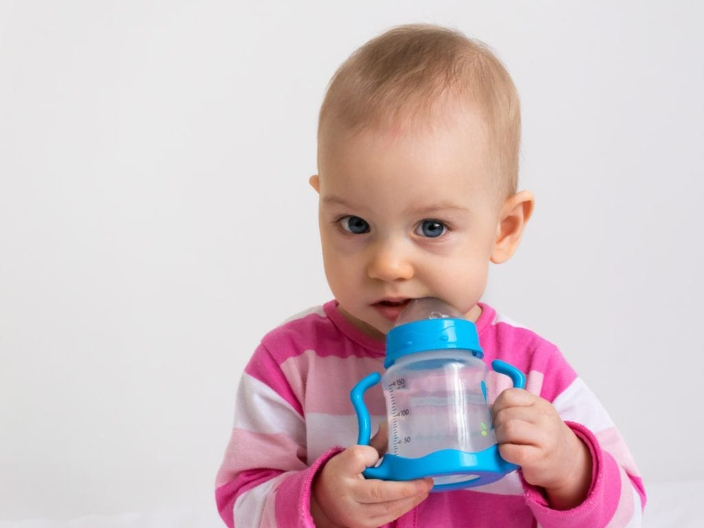 infant with water-filled bottle