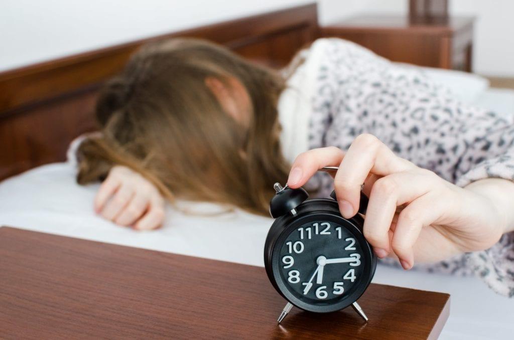 teenage girl hitting snooze on her alarm clock