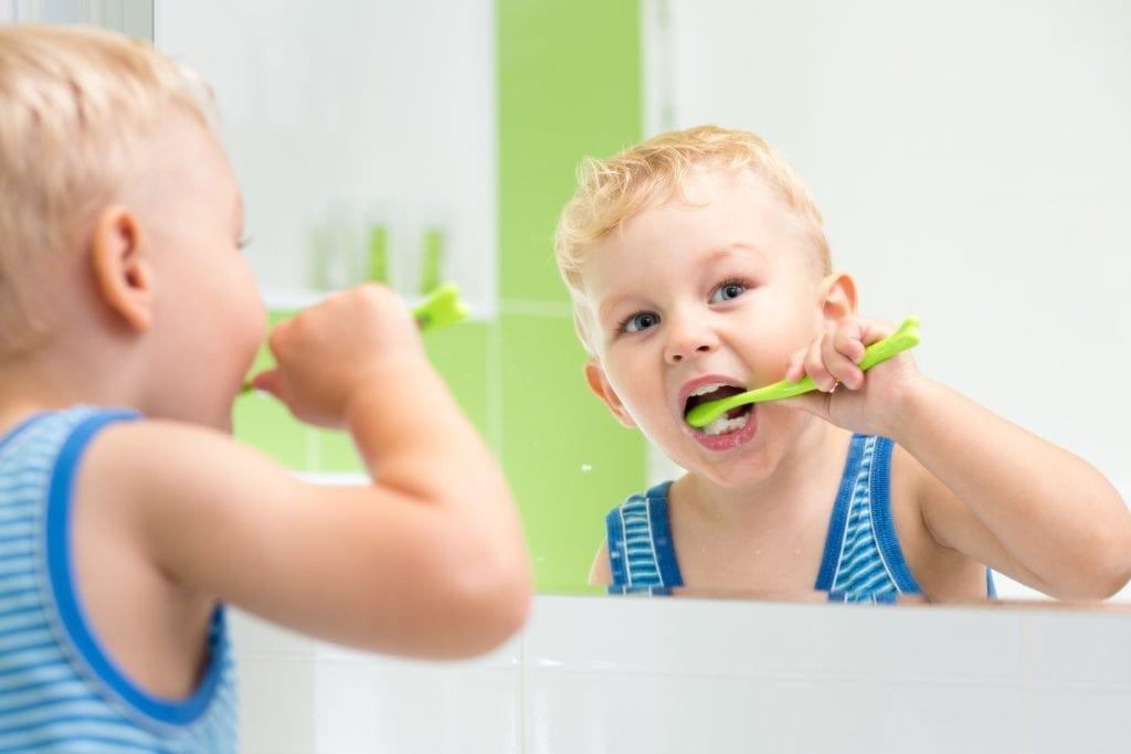 toddler boy brushing his teeth in the mirror