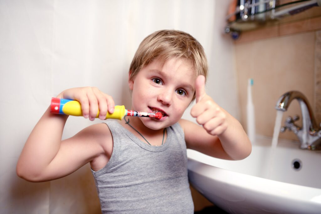 young boy brushing his teeth with an electric toothbrush