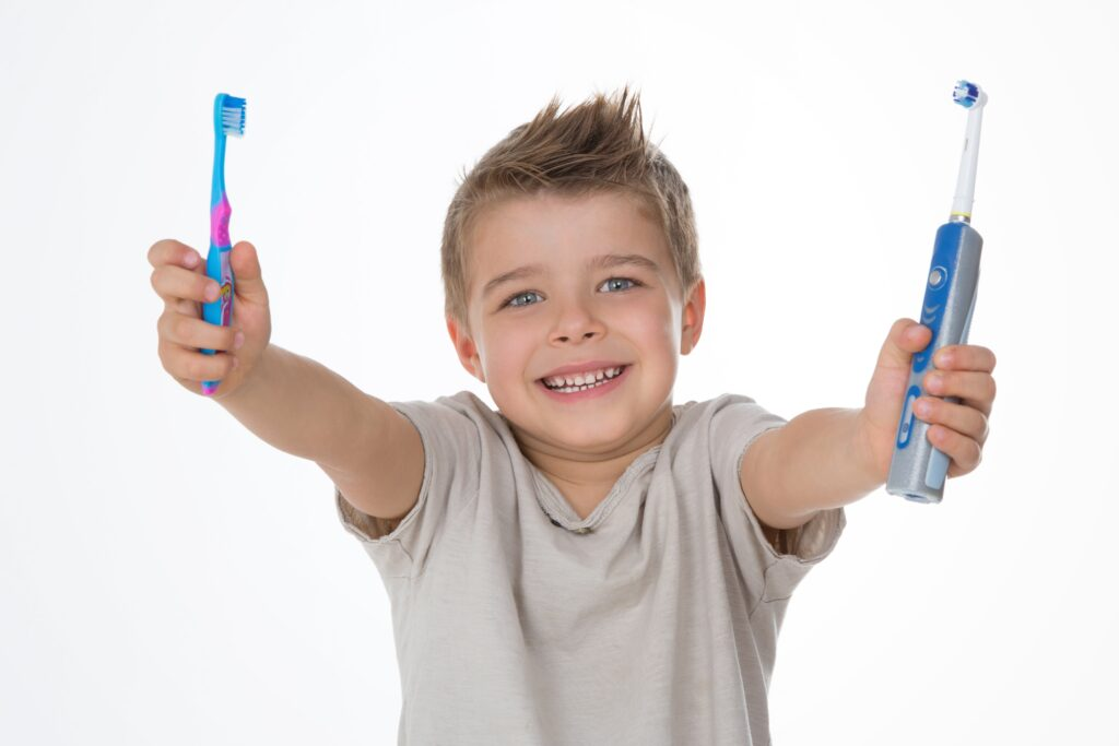 young boy holding an electric toothbrush in one hand and a manual toothbrush in the other