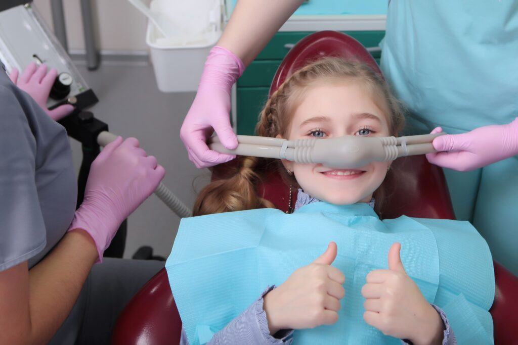 young girl in dentist chair wearing a sedation mask and giving thumbs up