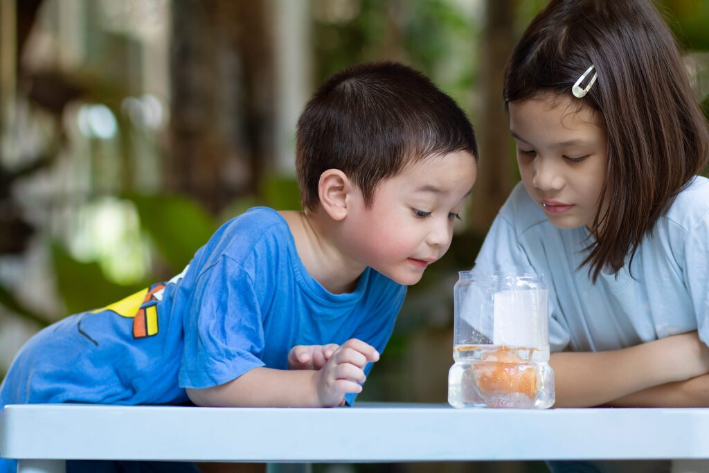 kids watching an egg in a jar