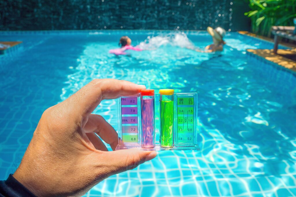 testing pH of swimming pool with mother and child in the background