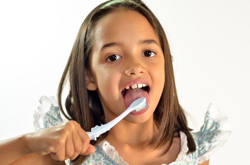 young girl brushing her tongue with toothbrush