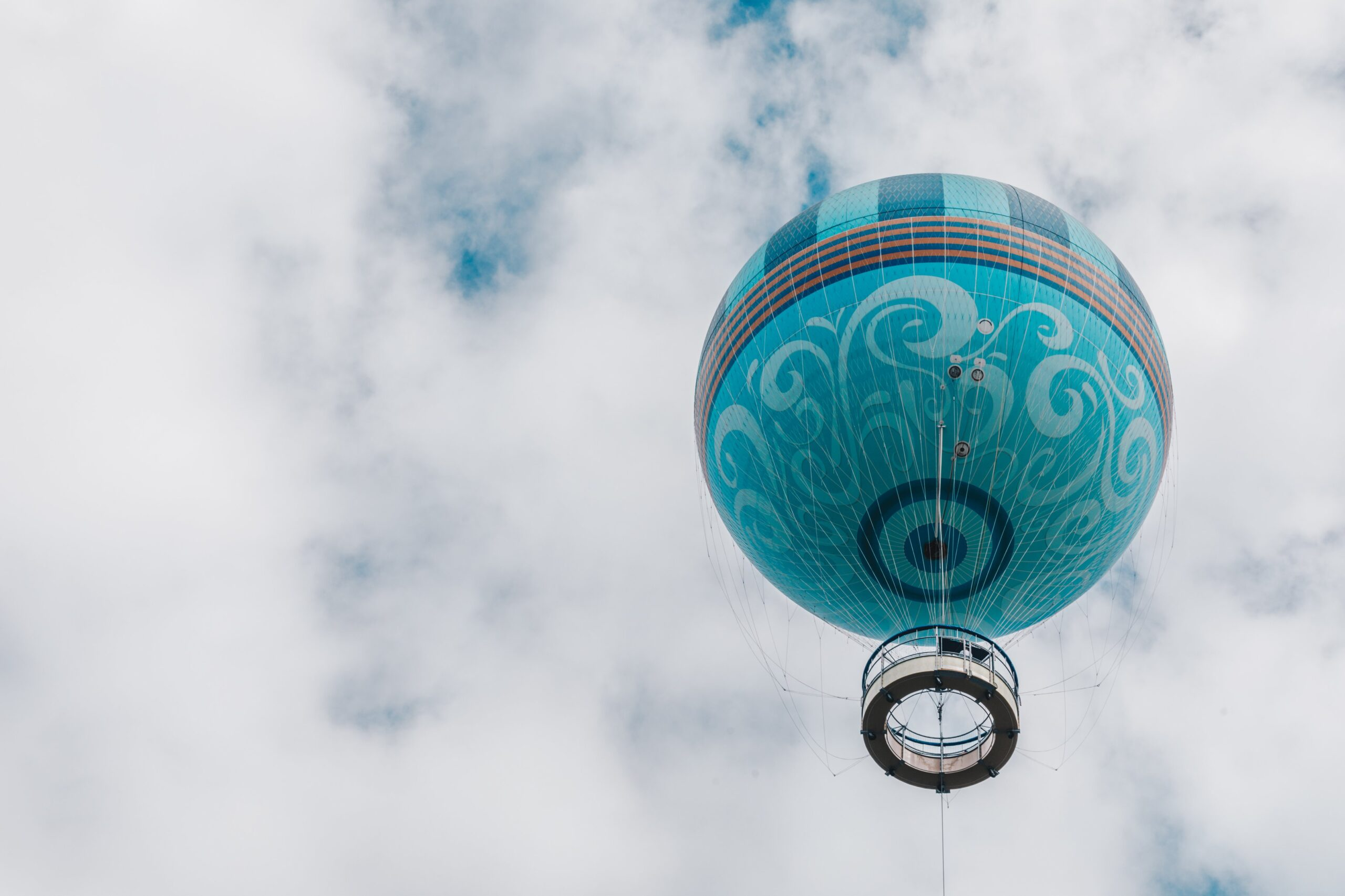 teal-hot-air-balloon-floats-up-into-white-puffy-clouds