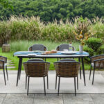 Muses Dining Set on an outdoor patio with grass and trees