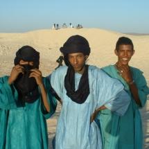 Young men standing in the dunes of Essakane, in the Sahara desert.