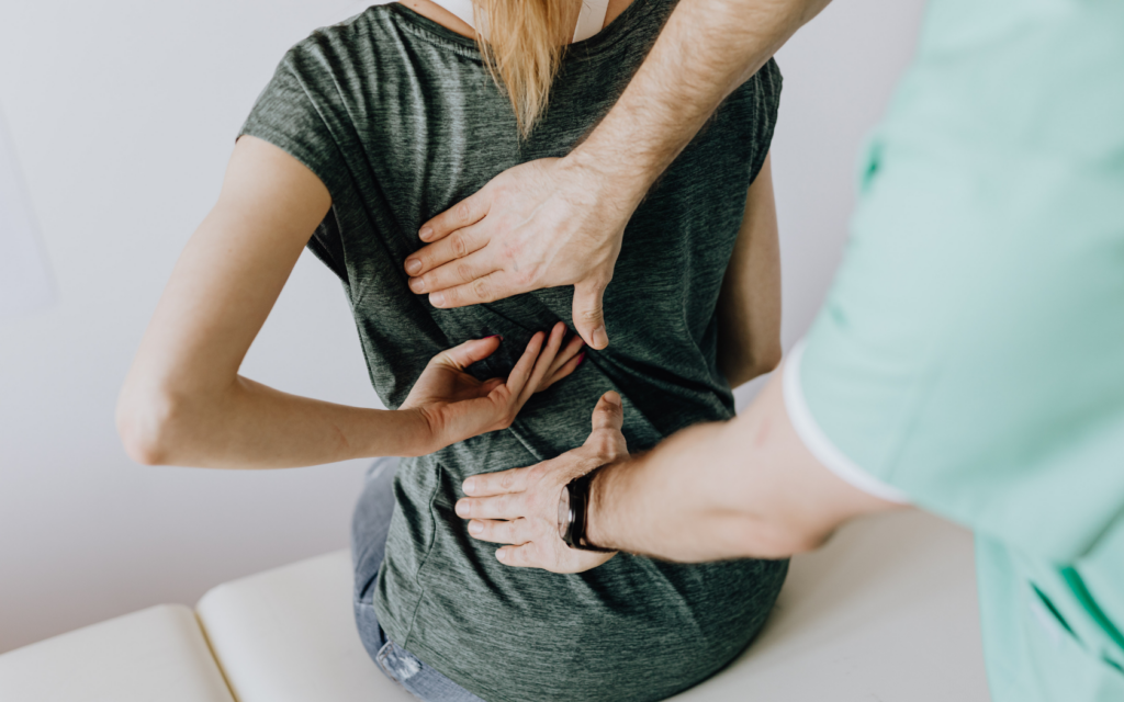 Chiropractor helps woman with back pain.