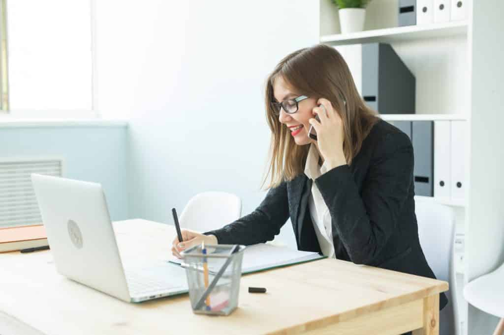 Business, realtor and people concept - Attractive woman in office talking on phone and make notes