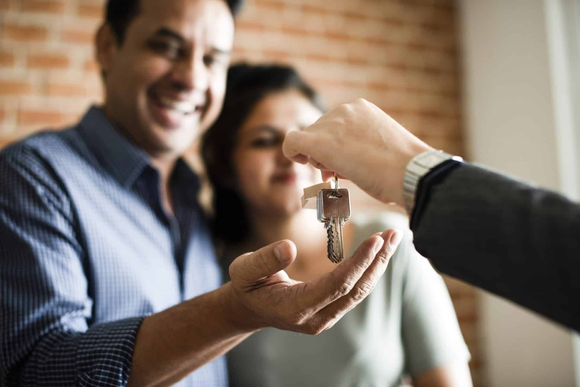 Cheerful couple with keys to their new home