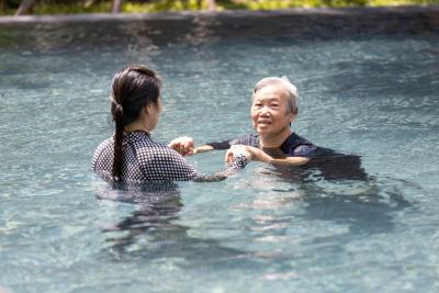 caregiver teaching senior woman to swim