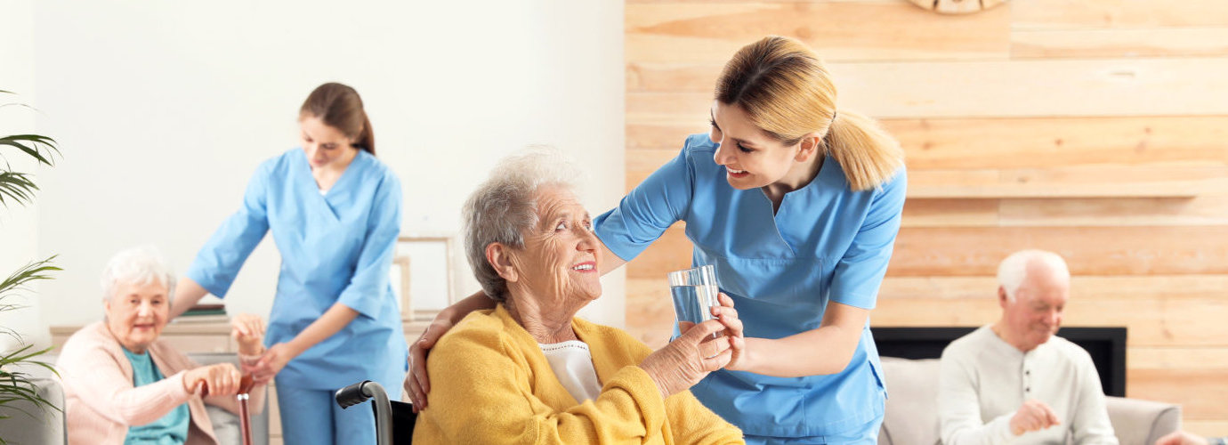 caregiver offering a glass of water to a senior woman