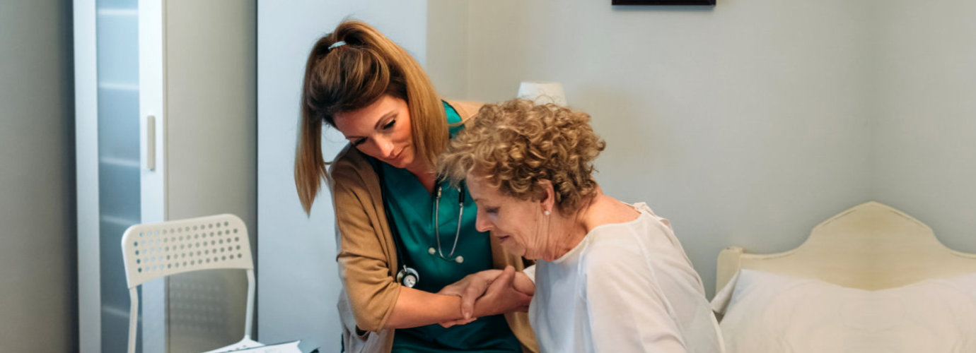 caregiver assisting senior woman to stand up