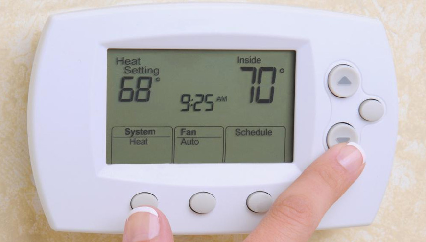 Technician installing a Thermostat for a baseboard heater