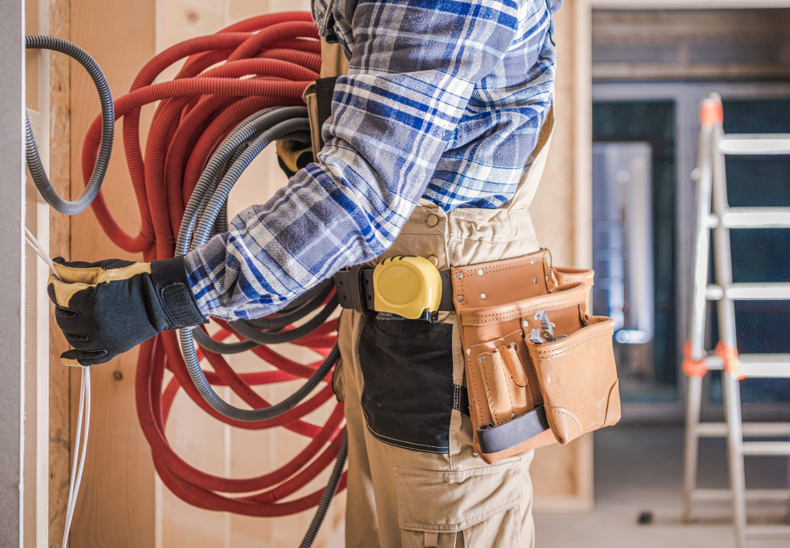 Caucasian Worker with Electric Cables Installing Residential Electric Lines Inside House.
