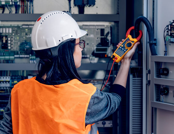 Female electrician checking the voltage of a power outlet