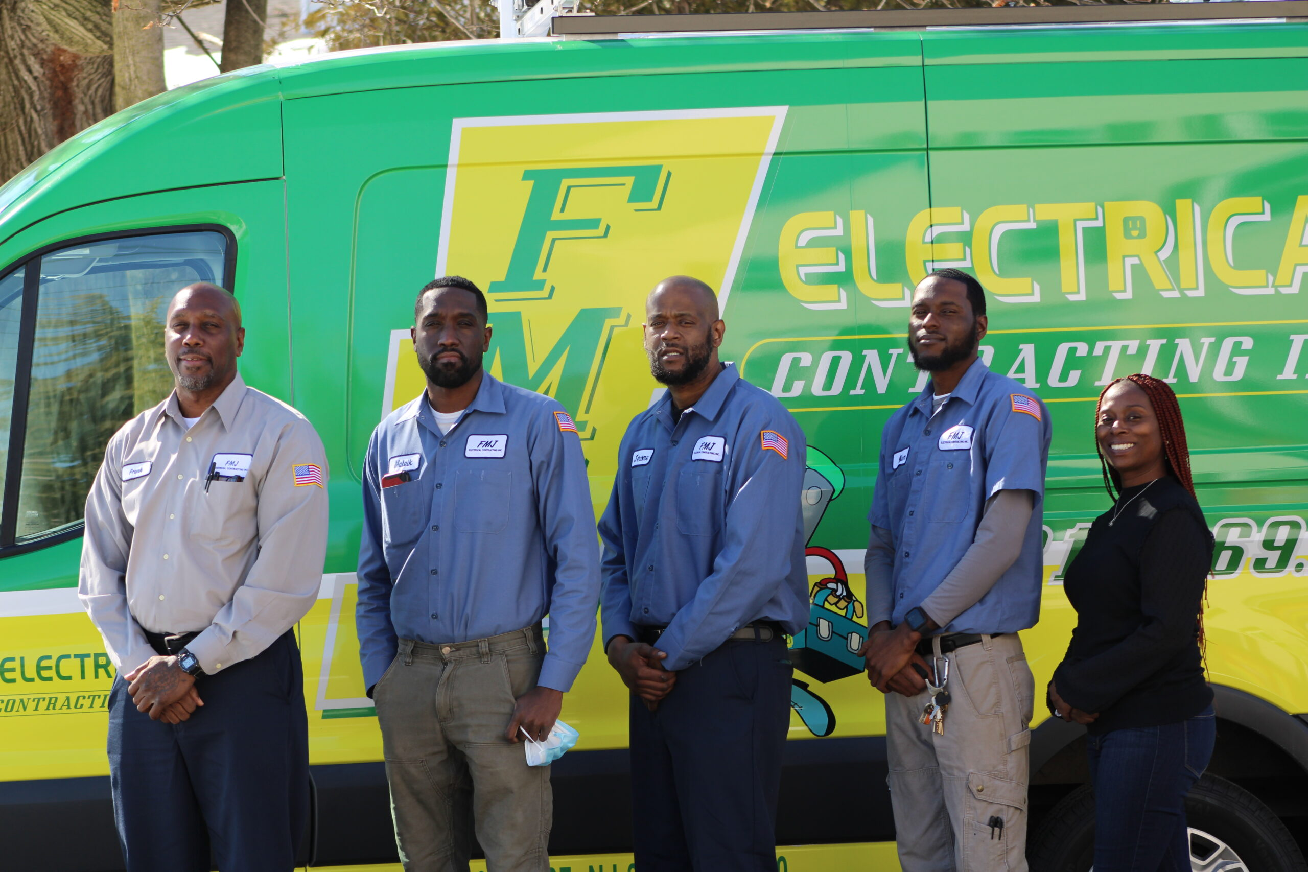 The Team at FMJ Electrical posing for a picture in front of two of the company vans