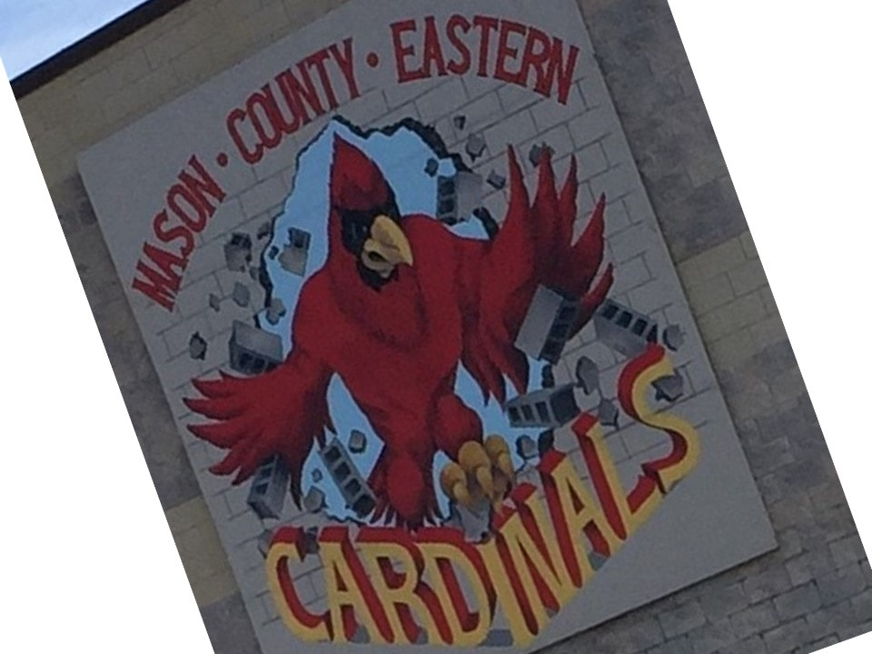 Mason County Eastern Schools Cardinals sign with Cardinal mascot breaking through a wall